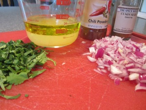 Cilantro, lime juice, olive oil, red onion, chili powder, and cumin ready to be added to beans.