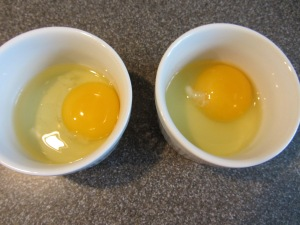 Eggs cracked into individual ramekins.