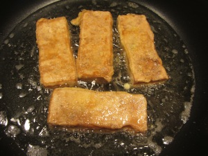 Tofu fillets flipped to cook on second side for two more minutes.