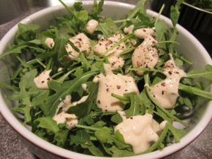 Tofu Caesar dressing over arugula.