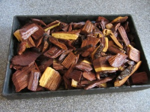 Soaked mesquite chips placed in smoking box.