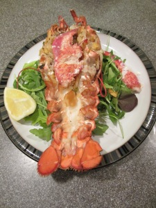 Final stuffed lobster with claw meat on top and lemon on the side.