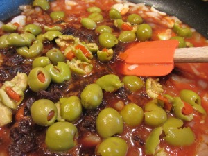 Tomato juice, balsamic vinegar, raisins, and green olives added to pan.