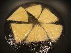 Frying corn tortilla wedges in corn oil.