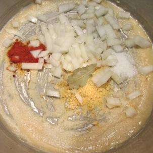 Powdered mustard, paprika, chopped onion, a bay leaf, and Kosher salt added to roux.