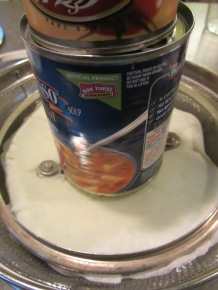 Seasoned yogurt, weighed down with a pan lid and cans.