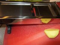 Slicing peeled potatoes into thin slices on a mandolin.