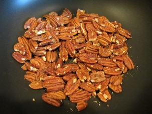 Pecans, toasting in a pan until fragrant.
