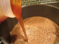 Warmed malt extract being added to the pot.