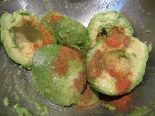 Kosher salt, cumin, and cayenne added to avocados.