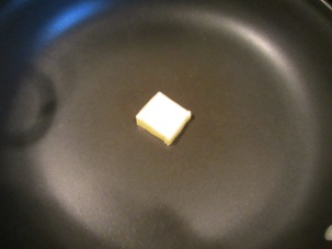 Large skillet with a pat of butter.