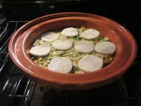 Rounds of puff pastry placed on chicken mixture, and placed in oven.