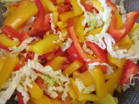 Shredded Napa cabbage, along with bell peppers, set aside to drain.