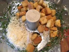 Garlic, parsley, oregano, rosemary, thyme, Parmesan, and croutons in the food processor.