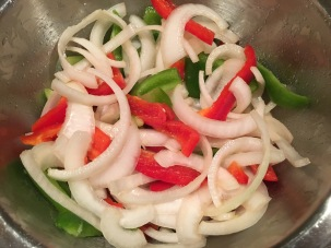 Sliced red bell pepper, green bell pepper, and white onion, tossed in vegetable oil.