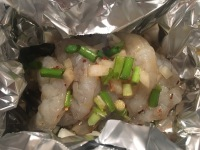 Foil balled up around shrimp and liquid ingredients added.