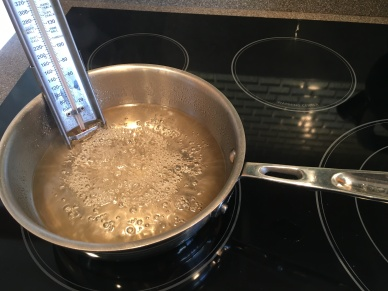 Heat decreased, thermometer in place, and syrup continuing to cook.