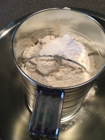 Flour, baking powder, and salt being sifted together.