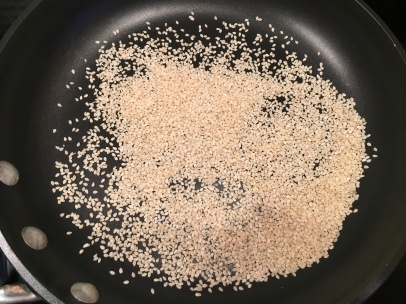 Sesame seeds, being toasted in a skillet.