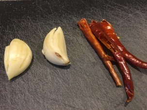 Two cloves of crushed garlic and three red chilies with their stems/seeds removed.