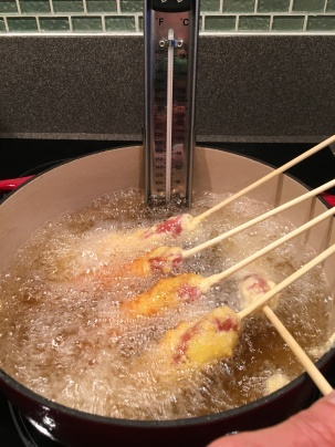 Corn dogs frying.