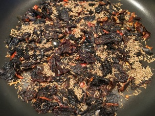 Cumin seeds added to dried chiles.