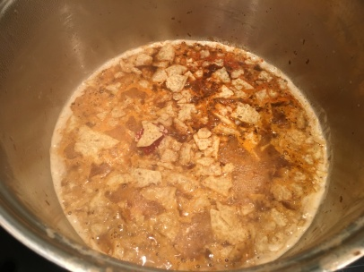 Tomato paste, chili powder, cumin, and tortilla chips added to beer.