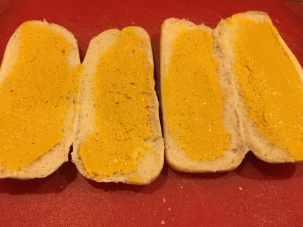 Hoagie rolls spread with yellow mustard.