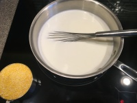 A cup of coarse cornmeal to be added to liquid.