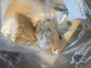 Seasoned chicken pieces in plastic bag with flour.