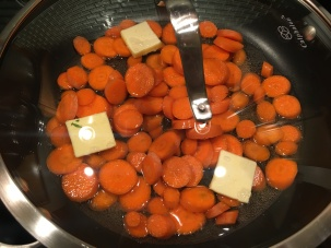 Carrots, Kosher salt, butter, and ginger ale in a skillet over medium heat. Lid placed on the pan.