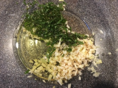 Garlic, mint, red wine vinegar, and olive oil in a bowl.