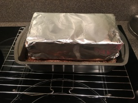 Foil-wrapped brick resting on meat while it cools.