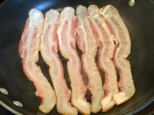 Bacon frying in large skillet.