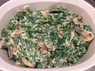 Greens/mushrooms placed in buttered baking dish.