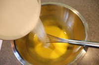 Slowly whisking sugar into yolks.
