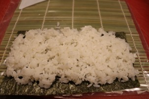 Sushi rice pressed onto Nori. Then sprinkled with sesame seeds.