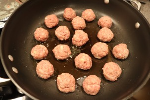 Meatballs browning in clarified butter.