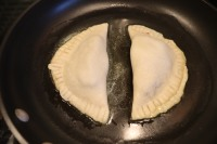 Chocolate pies frying in a pan with butter.